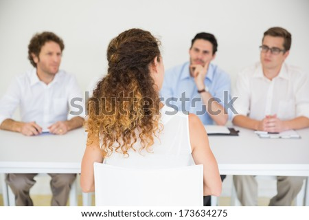 Panel of interviewers conducting job interview with female candidate - stock photo