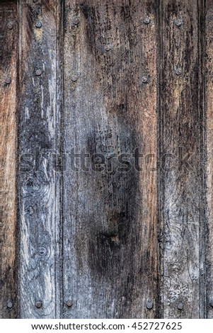 Panel of old faded and flaking wood studded with rusty nails for background texture - stock photo
