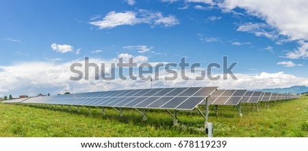 Panels of the solar energy plant under the blue sky with white clouds - clean energy concept; stitched panorama