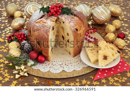 Panettone christmas cake and slice with bauble decorations, holly and winter flora over oak background with stars. - stock photo