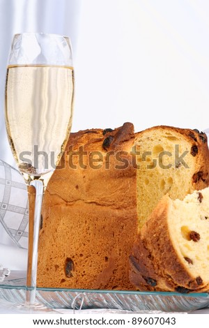 Panettone the italian Christmas fruit cake served on a transparent glass plate, a glass of spumante and some ornaments. Selective focus, shallow DOF. - stock photo