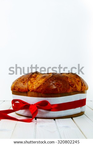panettone with a red bow on white  - stock photo
