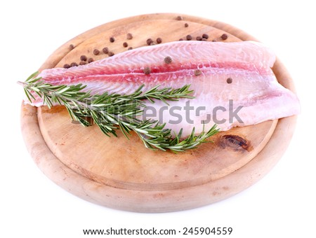 Pangasius fillet on wooden cutting board with pepper and rosemary sprigs isolated on white - stock photo
