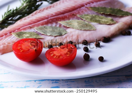 Pangasius fillet with herb and sliced cherry tomatoes on plate and color wooden table background - stock photo