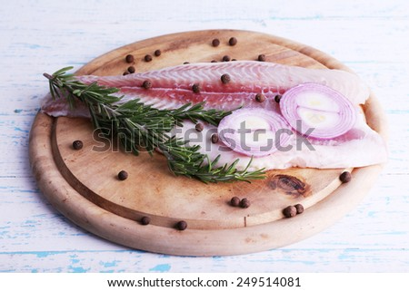 Pangasius fillet with herb and spices on cutting board and color wooden table background - stock photo