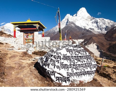 PANGBOCHE, NEPAL, 24th NOVEMBER 2014 - Pangboche monastery, stone with buddhist symbols and mount Ama Dablam, Khumbu valley near Tengboche, way to Everest base camp, Sagarmatha national park, Nepal - stock photo