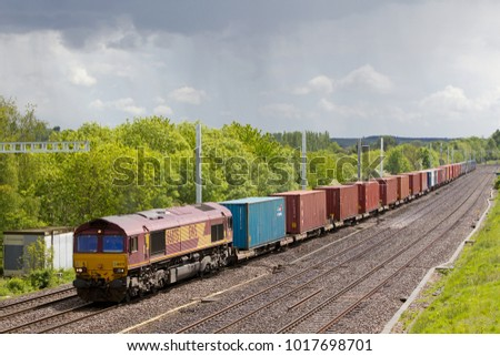 Pangbourne, UK - MAY 19: A DBS operated intermodal freight train passes under the recently installed electrification catenary on the GWR as it heads towards Southampton on May 19, 2015 in Pangbourne
