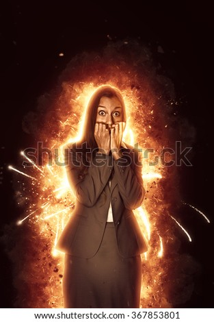 Panic stricken young Indian businesswoman surrounded by burning flames staring wide-eyed at the camera and biting her nails in a conceptual image over a dark shadowy background - stock photo