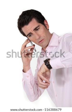 Panicked man calling in to work to say he'll be late - stock photo