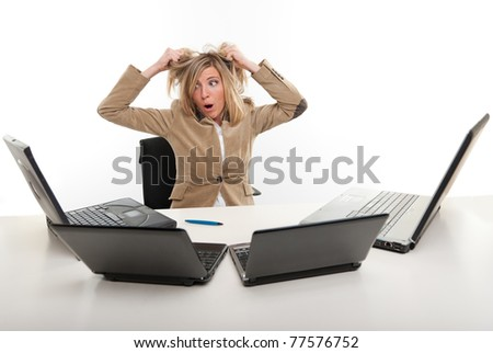 Panicked young woman in front of four laptops - stock photo