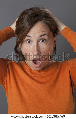 panicking middle aged woman with mouth opened and wide-eyed expressing surprise facing danger over grey background