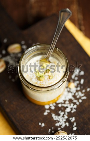 Panna cotta with mango, coconut and pistachios on a wooden cutting board - stock photo