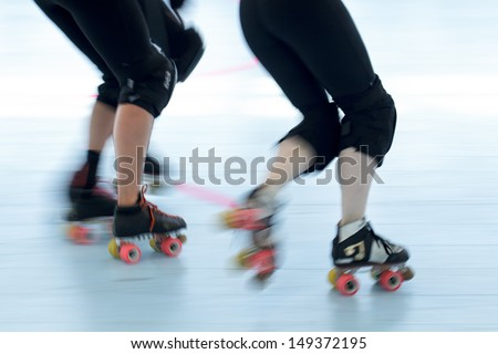 Panning action shot of skaters in a roller derby. Pan with motion blur. - stock photo