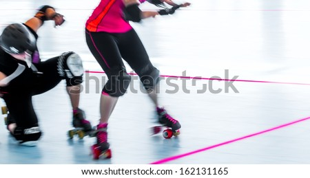 Panning action shot with motion blur of skaters in a roller derby, one falling down. Copy space. - stock photo