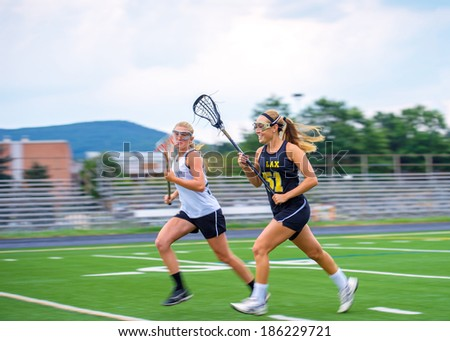 Panning blur featured as two female lacrosse players race down the field. High degree of motion conveyed. Some motion blur on athletes, particular in extremities, focus on face of closest player. - stock photo