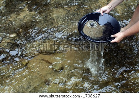 Panning for gold in a northern michigan stream - stock photo