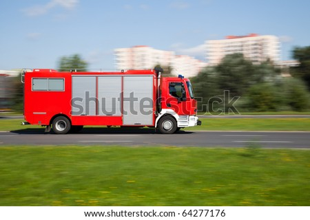 Panning image of a fire truck rushing on the street in intentional motion blur - stock photo