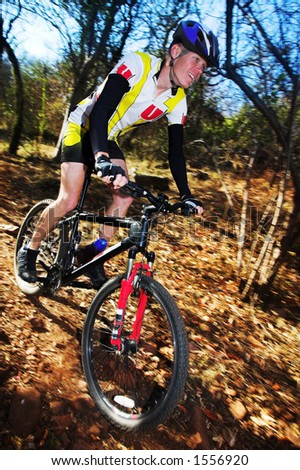 Panning shot of a mountain biker, racing in a forest.  Movement on background and some of the bike.  Face of biker in focus.