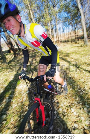 Panning shot of a mountain biker, racing in a forest. Panning:  movement on background and some of the bike and biker.  Focus on body of the racer.