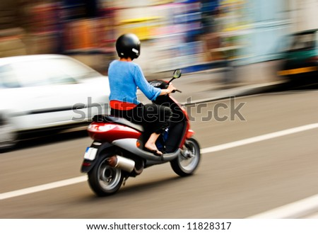 Panning shot of a young girl riding a scooter in a European city - stock photo