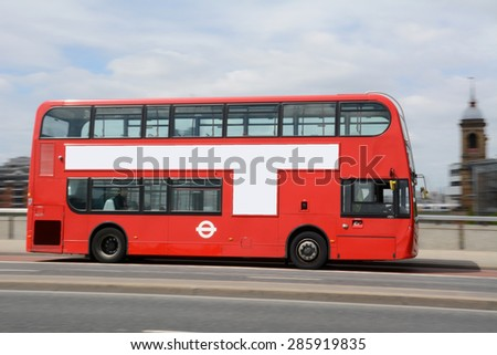Panning shot of red double decker bus in London. - stock photo
