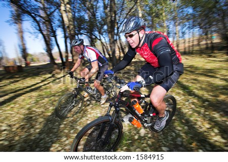Panning shot of two mountain bikers, racing in a forest.  Movement, some of the bikers in focus. - stock photo
