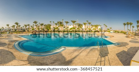 Panorama at beautiful swimming pool and palm trees in Egypt  - stock photo