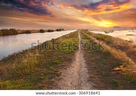 panorama at sunset of the wetland, a long straight path across the lagoon in the natural reserve Valli di Comacchio, near Ferrara, Emilia Romagna, Italy - stock photo