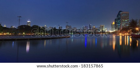 panorama beautiful dusky sky of modern building and city life landmark in heart of bangkok capital of thailand office building and reflection on water pool against twilight sky  - stock photo