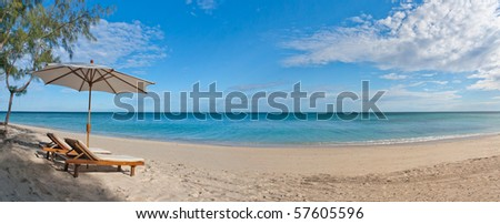 Panorama deckchair and parasol on the white sand beach facing the lagoon