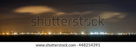 Panorama far view of with flare stack of cargo ship and crane at port at night in Thailand