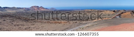 Panorama from volcanic hill on Lanzarote. Canary Islands. Timanfaya National Park. Ocean in background. - stock photo