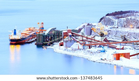 Panorama Industrial Container Cargo freight ship with working crane in shipyard at Iron Ore Mine Factory Plant in Narvik Norway - stock photo