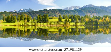 panorama landscape in Bavaria at alps mountains with perfect mirroring in lake - stock photo