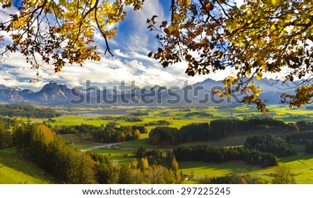 panorama landscape in Bavaria with alps mountains, meadows and beech tree at autumn
