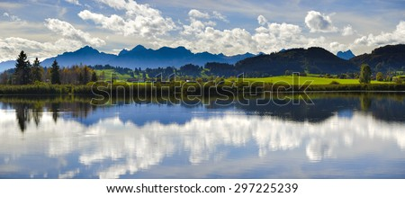 panorama landscape in Bavaria with alps mountains mirroring in lake - stock photo