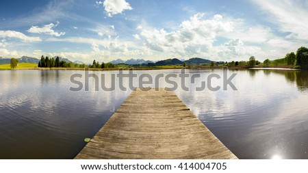 panorama landscape in Bavaria with lake and wooden swimming pier - stock photo