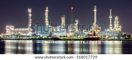 Panorama landscape of Oil refinery plant along river with tanker at night - stock photo
