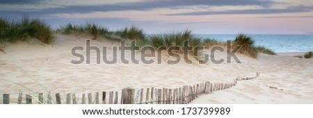 Panorama landscape of sand dunes system on beach at sunrise - stock photo