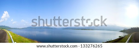 panorama lanscape lake and mountain. Path along the lake with the mountains behind the lake and forest. - stock photo