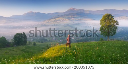Panorama morning landscape in a mountain village. Young man enjoying the first rays of the sun at dawn. Carpathian mountains, Ukraine, Europe - stock photo