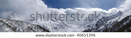 Panorama. Mountain peaks in the clouds