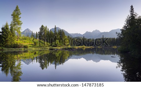 Panorama of a beautiful lake in a mountain resort surrounded by woods. Slovakia, lake Strbske Pleso less