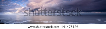 Panorama of a clearing storm over the ocean at dusk. - stock photo