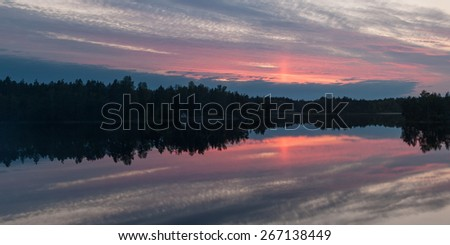 panorama of a cloudy decline over lake - stock photo