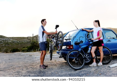 Panorama of a couple who have finished mountain biking outdoors and are loading the bicycles onto the car bike rack. large image, lots of copyspace, healthy lifestyle scene. - stock photo