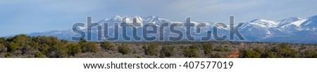 Panorama of a desert landscape with snow capped mountains in the distance  - stock photo
