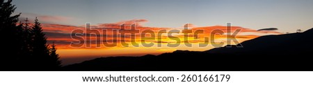 Panorama of a Mountain Sunrise with forest and a mountain ridge - stock photo