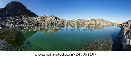 panorama of a still clear mountain lake with rocks on the bottom and reflection - stock photo