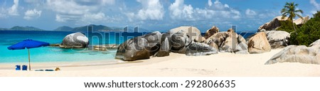 Panorama of a stunning beach with blue umbrella, white sand and turquoise ocean water at tropical island in Caribbean - stock photo